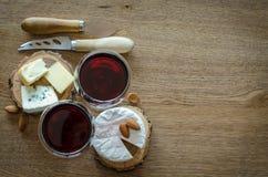 Dois vidros do vinho tinto com poucas partes de queijo e de facas no wo Imagem de Stock