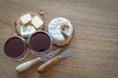 Dois vidros do vinho tinto com poucas partes de queijo e de facas no wo Imagem de Stock Royalty Free