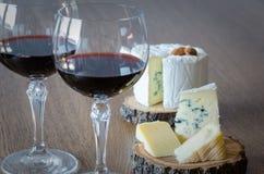 Dois vidros do vinho tinto com poucas partes de queijo no backgr de madeira Fotografia de Stock