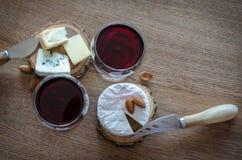 Dois vidros do vinho tinto com poucas partes de queijo no backgr de madeira Imagens de Stock