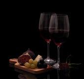 Dois vidros do vinho tinto com queijo, aumentaram, figos e uvas Foto de Stock