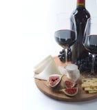 Dois vidros do vinho tinto, do queijo de cabra e do figo Imagens de Stock Royalty Free