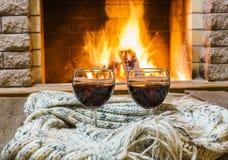 Dois vidros do vinho tinto e as coisas de lã aproximam a chaminé acolhedor Foto de Stock Royalty Free
