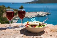 Dois vidros do vinho tinto e da bacia da salada grega com bandeira grega sobre pela opinião do mar, conceito grego dos feriados d Imagens de Stock Royalty Free