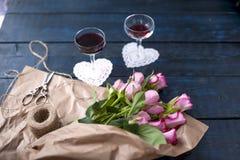 Dois vidros do vinho tinto em uma tabela escura, um ramalhete de rosas cor-de-rosa no papel marrom Dois corações e biscoitos bran Fotos de Stock