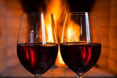 Dois vidros do vinho tinto no fundo do fogo Imagens de Stock Royalty Free
