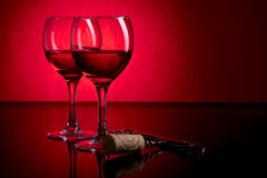 Dois vidros do vinho tinto no fundo vermelho e preto Fotografia de Stock