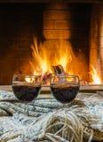 Dois vidros do vinho tinto perto da chaminé acolhedor Imagem de Stock
