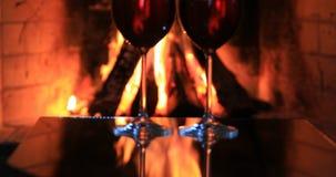 Dois vidros do vinho tinto perto de uma chaminé vídeos de arquivo
