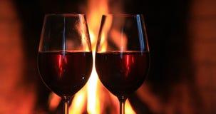 Dois vidros do vinho tinto perto de uma chaminé video estoque