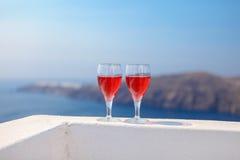 Dois vidros do vinho tinto saboroso no por do sol em Grécia Imagens de Stock