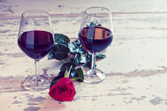 Dois vidros do vinho vermelho e de uma rosa imagem de stock