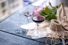 Dois vidros do vinho vermelho Um ramalhete de rosas cor-de-rosa no papel marrom e nas tesouras, perto da janela Dois corações bra Fotos de Stock Royalty Free