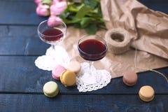 Dois vidros do vinho vermelho Um ramalhete de rosas cor-de-rosa no papel marrom e nas tesouras, perto da janela Dois corações bra Imagens de Stock