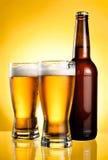 Dois vidros e frascos da cerveja clara fresca Fotografia de Stock