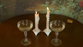 Dois vidros na tabela de madeira Pares de alargamento das velas Fim candless de sopro acima Um córrego do fumo de uma vela extint video estoque