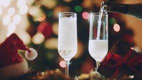 Dois vidros que enchem-se com o champanhe na noite dos anos novos foto de stock