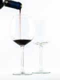 Dois vidros transparentes excelentes com vinho tinto e um vinho de derramamento da garrafa em um fundo branco Fotos de Stock Royalty Free