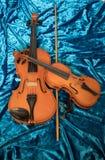 Dois violinos de tamanhos diferentes na tela azul fotografia de stock