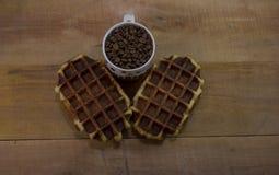 Dois waffles doces com o copo completo de feijões de café Fotografia de Stock Royalty Free
