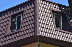 Dois Windows na mansarda bonita com metal shingles enfrentar a rua da cidade fotos de stock royalty free