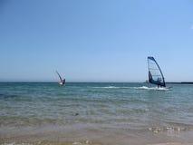 Dois windsurfers com uma vela azul e vermelha no mar Imagens de Stock