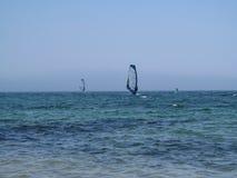 Dois windsurfers são ficados simetricamente na superfície do mar Imagem de Stock Royalty Free