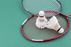 Dois worned para fora a peteca do badminton com a raquete na corte verde Foto de Stock
