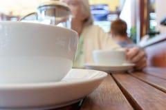 Dois xícaras de chá e franceses pressionam na tabela, mulher borrada atrás fotografia de stock royalty free