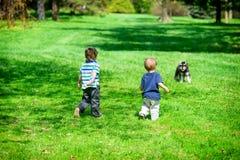 Dois Young Boys em um parque que aproxima um cão Fotografia de Stock Royalty Free