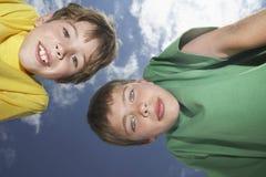 Dois Young Boys que dobra-se para baixo contra o céu Foto de Stock Royalty Free