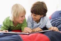 Dois Young Boys que encontram-se para baixo em uma cama que lê um livro Foto de Stock Royalty Free
