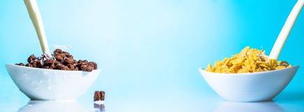 Dojny strumienia dolewanie w puchar z żółtymi i czekoladowymi Ñ  ornflakes, dojny pluśnięcie na filiżance z płatkami na błękitny Zdjęcie Stock