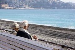 Dojrzała, z włosami piękna para: mężczyzna i kobieta jesteśmy siedzący na białej ławce na Promenade Des Anglais i patrzeć zdjęcia stock