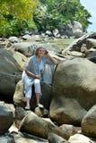 Dojrzały kobiety obsiadanie przy piaskowatą plażą z skałami fotografia stock