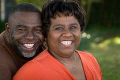 Dojrzała amerykanin afrykańskiego pochodzenia para śmia się i ściska obrazy royalty free