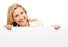 Dojrzała biznesowa kobieta opiera na białym sztandarze uśmiecha się odosobnionego o Obraz Stock