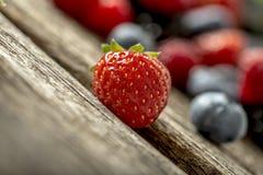 Dojrzała czerwona truskawka na nieociosanym drewnianym stole Obraz Royalty Free