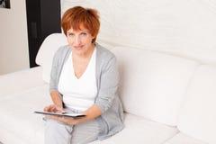 Dojrzała dorosła kobieta z pastylka komputerem osobistym Obraz Royalty Free