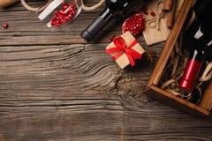 Dojrzała granatowiec owoc z szkłem wino, butelka i prezent na drewnianym tle, fotografia royalty free
