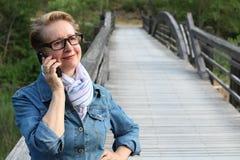 Dojrzała kobieta czeka twój wezwanie z szkłami Ubierający w drelichowej kurtce, starsza Kaukaska dama stoi rzeka mostem obrazy stock
