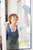 Dojrzała kobieta czyści nadokiennego cleaning okno fotografia royalty free