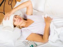 Dojrzała kobieta kłaść w łóżku z ręcznikiem Fotografia Stock