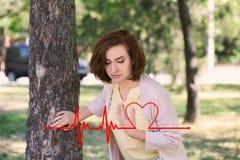 Dojrzała kobieta ma atak serca blisko drzewa obraz royalty free
