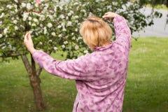 Dojrzała kobieta obejmuje owocowego drzewa zdjęcie royalty free