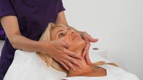 Dojrzała kobieta ono uśmiecha się podczas twarzowego masażu przy piękno salonem obrazy stock
