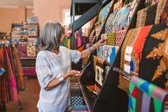 Dojrzała kobieta patrzeje kolorową tkaninę w jej sklepie Fotografia Royalty Free