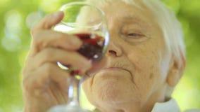Dojrzała kobieta pije czerwone wino zbiory