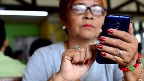 Dojrzała kobieta scrolling w górę mądrze telefonu interneta wyszukiwać zbiory wideo
