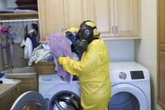 Dojrzała kobieta sortuje pralnię w Haz maty kostiumu Obraz Stock